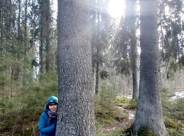 Nainen nojaa puuhun metsässä.
