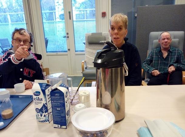 Kuvassa istuu kolme miestä pöydän äärellä ja pöydällä on termoskannu