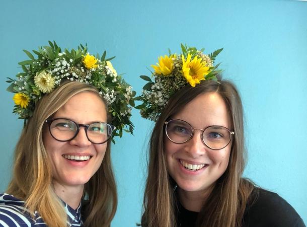 Kaksi hymyilevää naista, joilla on kukkaseppeleet päässä