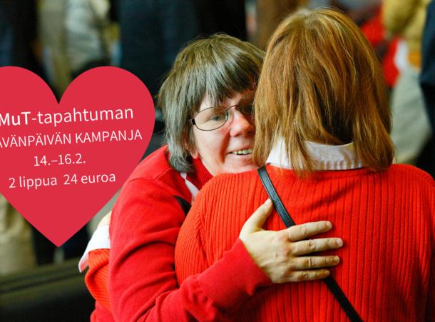 kuvassa kaksi punapaitaista naista halaamassa toisiaan.