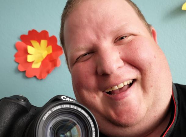 kuvassa iloinen ihminen kamera kädessä