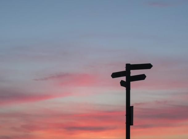 kyltti joka osoittaa eri suuntiin, taustalla auringonlasku
