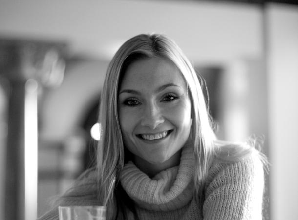 Ammattikokki Teresa Välimäki nojaa pöytään ja hymyilee kameralle