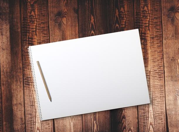puisella pöydällä vihko, jossa ei ole mitään kirjoitusta. Vihkon päällä on kynä.